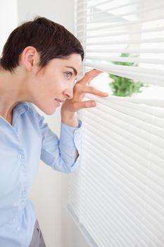 Good-looking woman peeking out a window