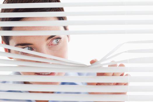 Charming businesswoman peeking through a venetian blind
