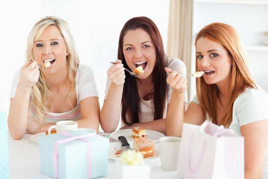 Good-looking Women sitting at a table eating a cake