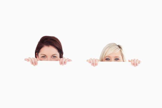 Women peeking over a banner