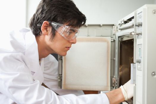 Close up of a scientist using a laboratory chamber furnace