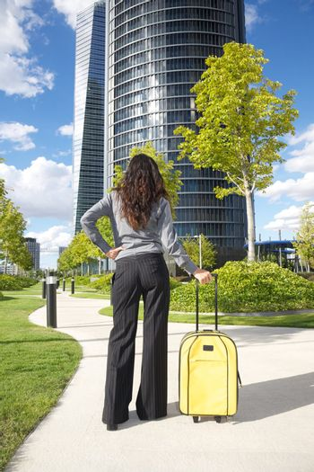businesswoman stands with suitcase