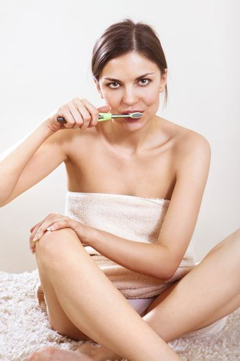 beautiful woman with tooth-brush cleans her teeth