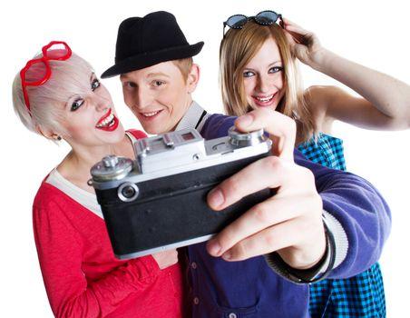 Three joyful teenage friends with old photo camera