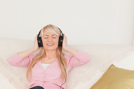 Good looking woman listening to music on her headphones while si