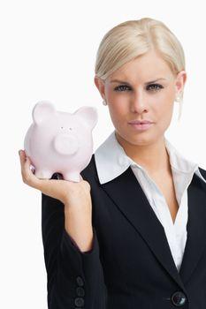 Stern businesswoman holding a piggy-bank