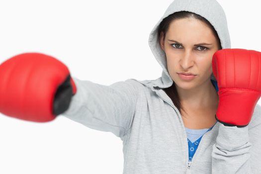 Stern woman in sweatshirt boxing