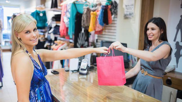 Woman taking shopping bag at cash register