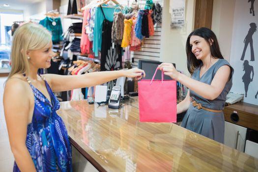 Woman handing over shopping bag at cash register