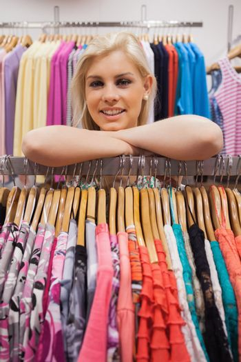 Woman lean on a clothes rack looking satisfied
