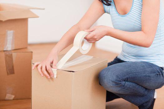 feminine hands taping a box