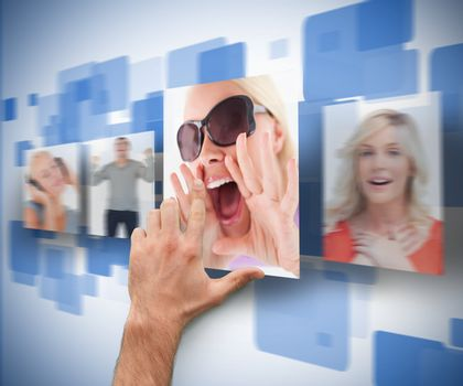 Male hand selecting picture from digital blue wall