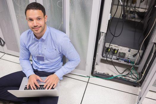 Man smiling while doing server maintenance