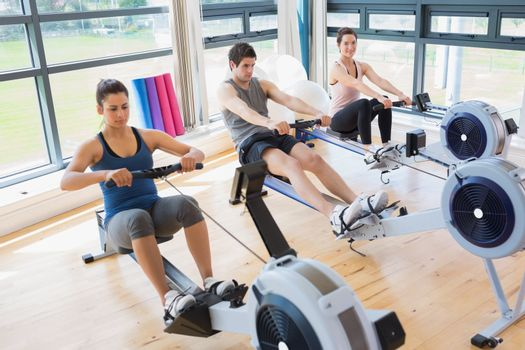 Three people on rowing machines