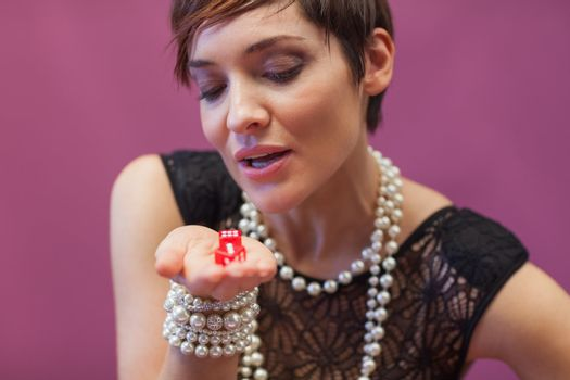 Woman blowing on dice for luck