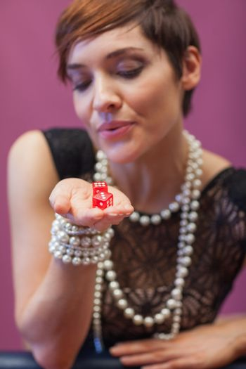 Dice being blown on by woman for luck