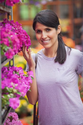 Smiling woman about to smell flowers