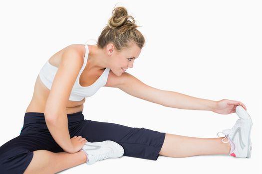 Woman sitting while stretching leg