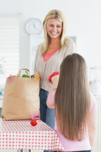 Mother and daughter unpacking grocery bag