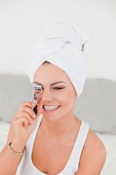 Portrait of a brunette curling her eyelashes