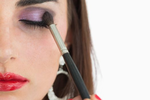 Woman getting applied red lips and smoky eyes