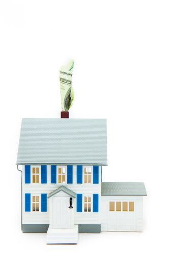 House with money coming out of the chimney