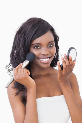 Woman smiling while holding powder compact