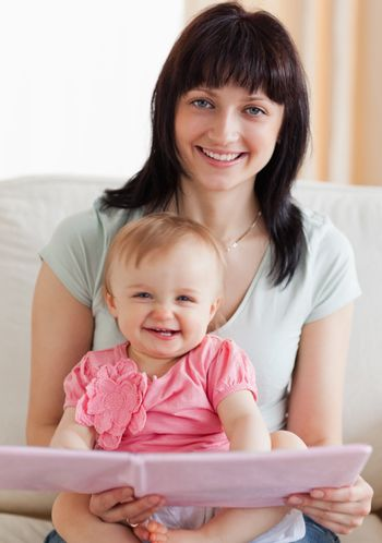 Beautiful woman holding her baby and a book in her arms while si