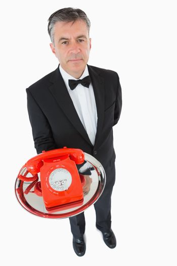 Waiter holding a red dial phone