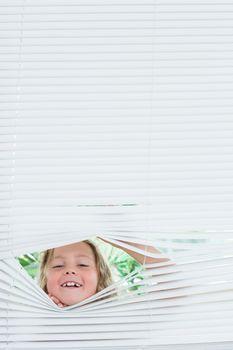 Girl peeking out of blinds