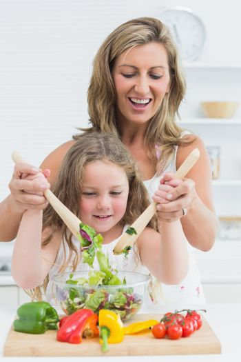 Mother and daughter mixing salad