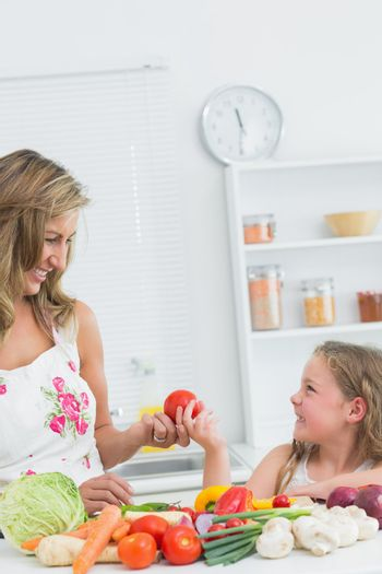 Daughter giving tomato to mother