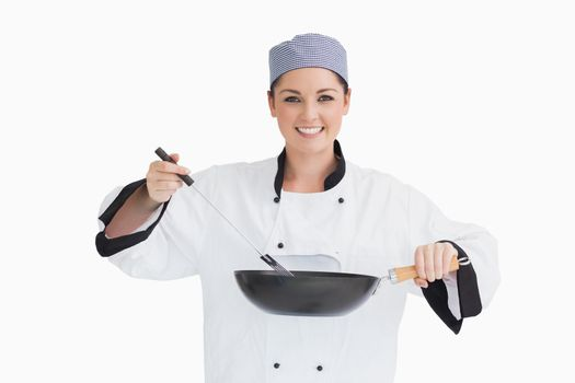 Happy cook cooking with wok and spoon