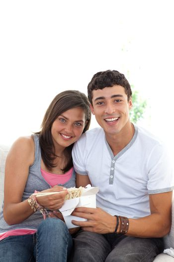 Couple of teenagers eating pasta with copy-space