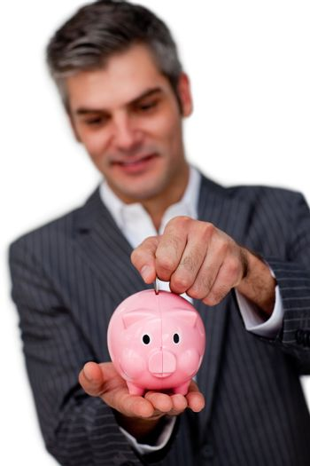 Sophisticated male executive saving money in a piggybank