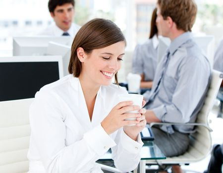 Smiling businesswoman holding a cup of coffee in the office