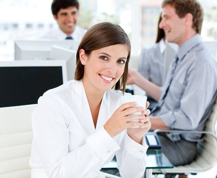 Smiling businesswoman holding a cup of tea in the office