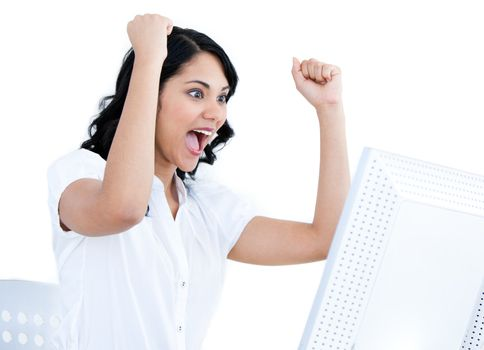 Enthousiastic businesswoman punching the air in front of her com
