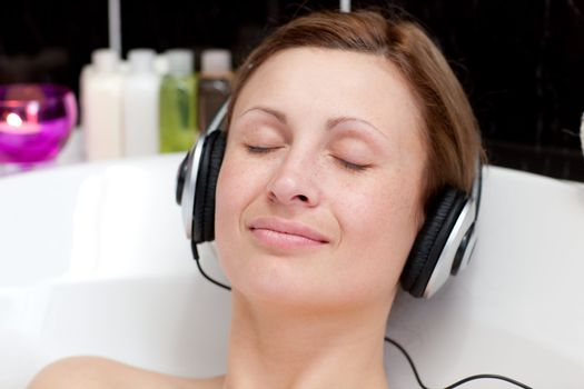 Close-up of a relaxed young woman listening music in a bubble ba