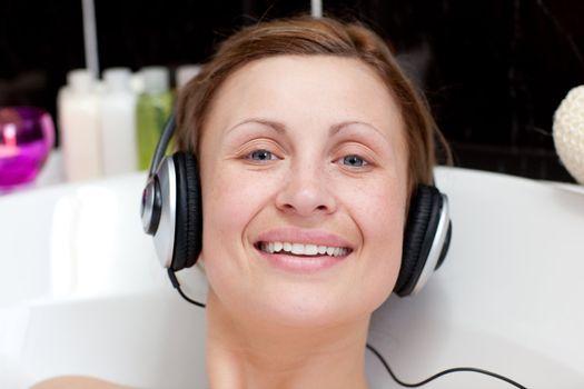 Cheerful woman using headphones in a bubble bath