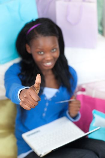 Cute teen girl with thumb up shopping on-line