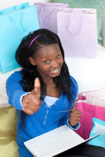 Smiling teen girl with thumb up shopping on-line