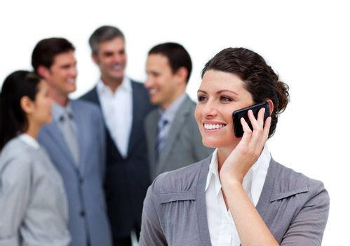 Caucasian woman talking on phone in front of her team against a white background