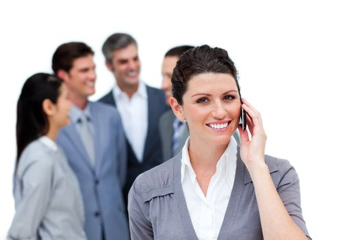 Brunette woman talking on phone in front of her team against a white background