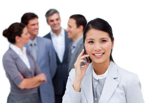 Jolly businesswoman talking on phone in front of her team against a white background