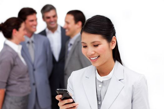 Asian businesswoman looking at her cellphone in front of her team against a white background