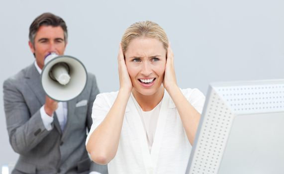Competitive manager yelling through a megaphone in his colleague