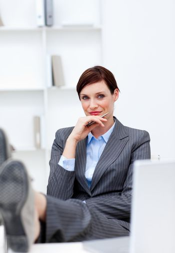 Satisfied Businesswoman sitting in office with feet on desk