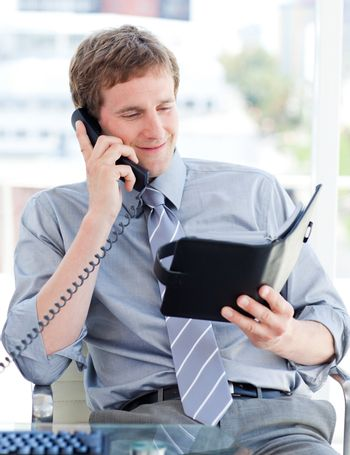 Serious businessman planning an appointment on phone