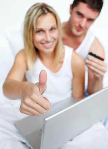 Couple in bed buying on-line successfully